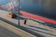 A woman walks along the Moskva River in Moscow