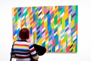 Woman in colourful striped jumper looking at Bridget Riley painting at Hayward Gallery Southbank London