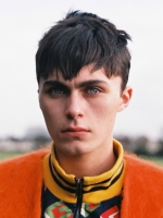 Fashion photography portrait of young English male model with light eyes and orange designer clothing